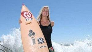 Bethany Hamilton - Standing on the beach with her surfboard with waves at the back.